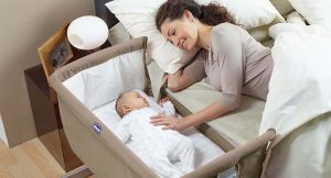 Berço Acoplado da fabricante Chicco. Mamãe deitada na cama ao lado do bebê no berço acoplado.