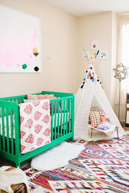 Berço colorido verde com elementos rosa no quarto.